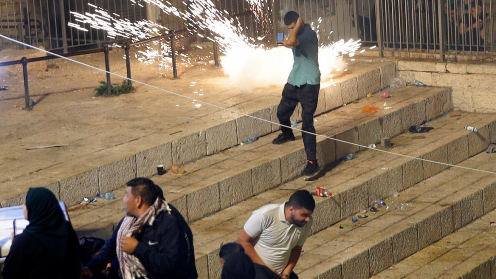 Palestinere løper fra sjokkgrenader avfyrt av israelske politistyrker i Jerusalems gamleby lørdag