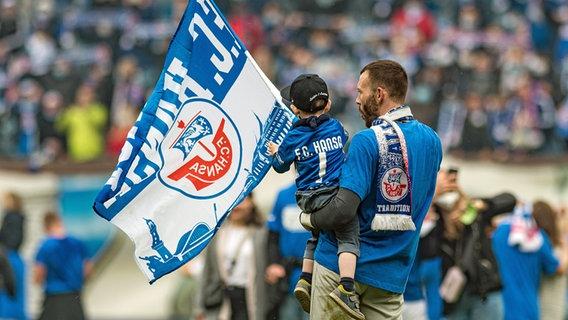 Hansa Rostock's goalkeeper Marcus Kolke celebrates promotion with his son in hand.  © IMAGO / Photo booth