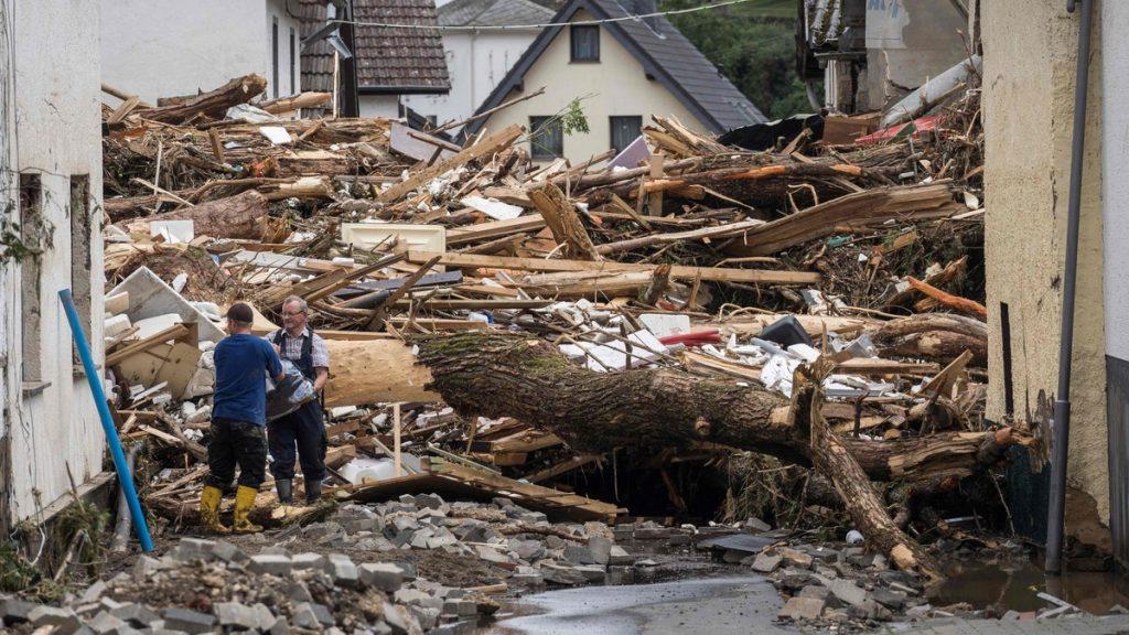 To menn fjerner forsøk på å sikre varer fra ved siden av rusk fra hus ødelagt av flommene i Schuld nær Bad Neuenahr, Vest-Tyskland, 15. juli 2021