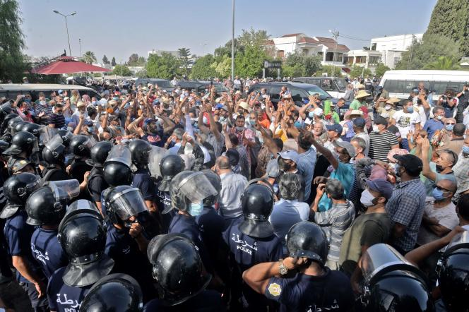 Tunisian police detain protesters outside the parliament building in the capital, Tunis, on July 26, 2021.