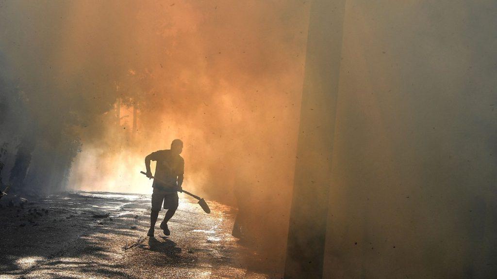En lokal innbygger løper for å bekjempe en brann i Thrakomakedones, nær Parnitha -fjellet, nord for Athen, 7. august